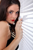Woman peering through blinds — Stock Photo