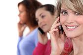 Jonge vrouwen praten over hun mobiele telefoons — Stockfoto