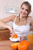 Blond woman freshly squeezing orange juice — Stock Photo