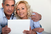 Middle-aged couple with computer — Stock Photo