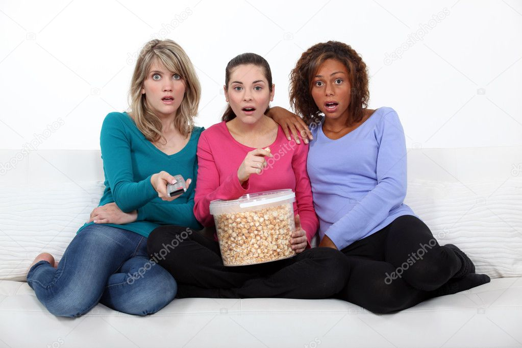 Three scared women sat on sofa watching movie  Stock Photo #10409209
