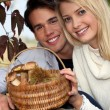 Stock Photo: Couple collecting chestnuts and mushrooms in forest