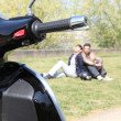 Stock Photo: Parked scooted next to couple