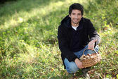 Man knelt by basket of mushrooms — Stock Photo