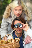 Couple with shopping and binoculars — Stock Photo