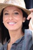 Attractive brunette wearing straw hat — Stock Photo
