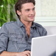 Young man listening to downloaded music — Stock Photo #10467068