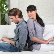 Couple back to back on sofa — Stock Photo #10467073