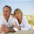 Couple lying in a sand dune — Stock Photo