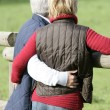 Royalty-Free Stock Photo: Married couple hugging by wooden fence