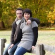 Couple sat on wooden fence - 