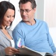 Couple reading sat on a couch — Stock Photo #10468365