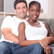 Couple sitting on sofa — Stockfoto