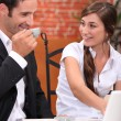 Couple with laptop in restaurant - Stock Photo