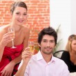 Smart couple drinking champagne at a party — Stock fotografie #10469763