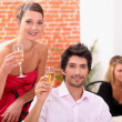 图库照片: Smart couple drinking champagne at a party