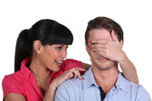 Young woman covering a man's eyes — Stock Photo