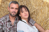 Couple leaning on haystack — Stock Photo