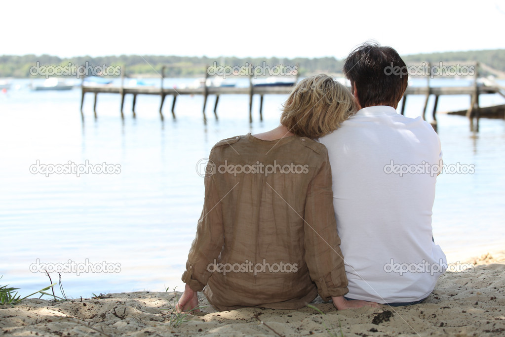 Couple sitting lakeside — Stock Photo #10468624