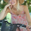 Woman with hat on a bicycle - Stock Photo