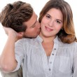 Stock Photo: Young man kissing his girlfriend