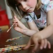 A little girl playing pick-up sticks — Stock Photo