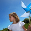 Little girl stood in filed with toy windmill — Stock Photo #10472325