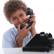 Stock Photo: Little boy calling with old telephone
