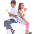 A brother and his sister enjoying a lollypop. — Stock Photo