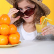 Little girl with freshly squeezed orange juice — Stockfoto