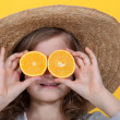 Young girl holding orange slices in front of her eyes — Stock Photo