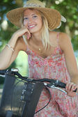 Woman with hat on a bicycle — Stock Photo
