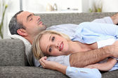 Couple lying on the couch — Stock Photo