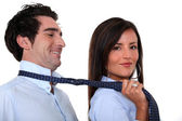 Woman leading a man by his tie — Stock Photo