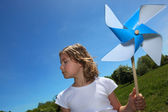 Little girl stood in filed with toy windmill — Stock Photo