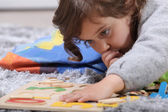 Child playing with a puzzle — Stock Photo