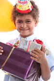 A little boy holding a conical hat and birthday gifts in his arms — Stock Photo