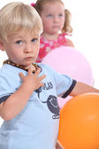 Young boy wearing an amber teething necklace and his friend playing with balloons — Stock Photo