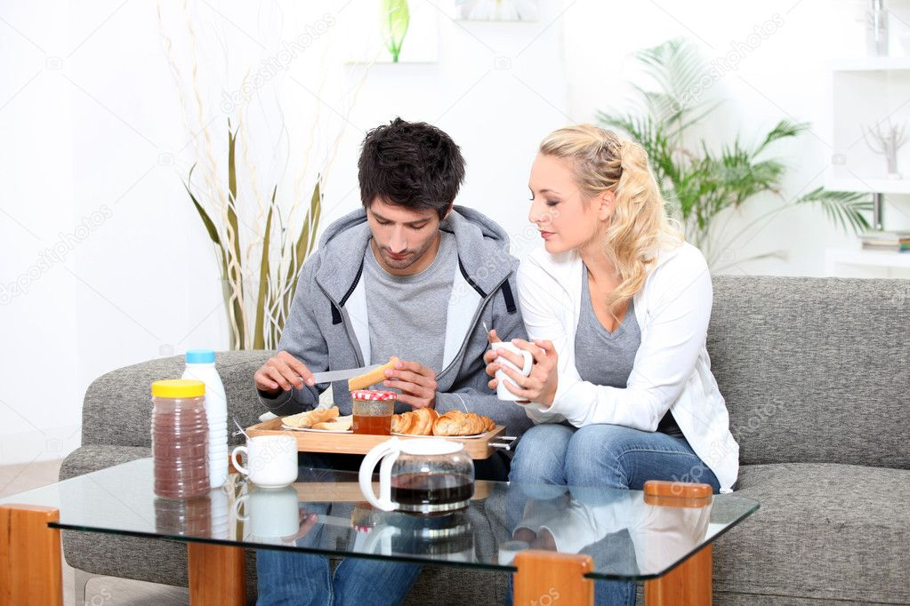 Couple having breakfast in their living room — Stock Photo #10470417
