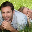Couple lying amongst the daisies — Stock Photo #10490094
