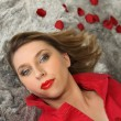 Stock Photo: Womlaying on rug next to rose petals