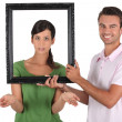 Playful couple stood with empty picture frame — Stock Photo