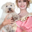 Stock Photo: Lady in pink and cream historical frock holding small white dog