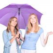 Two young blonde women under a umbrella, one of them is looking up and holding out one's hand — Stock Photo