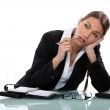 Pensive businesswoman sitting at a desk — Stock Photo