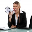 Businesswoman shouting angrily with loudspeaker and laptop — Stock Photo