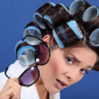 Stock Photo: Woman with her hair in rollers holding a pair of sunglasses