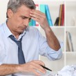 Businessman struggling at his desk — Stockfoto