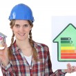 Stock Photo: Female heating engineer holding money box in shape of house