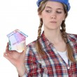Craftswoman holding a little model of house made of banknotes — Stock Photo